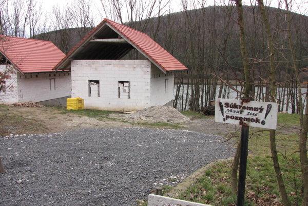 Rozostavané domy sú pri ceste, za nimi je vodná nádrž.