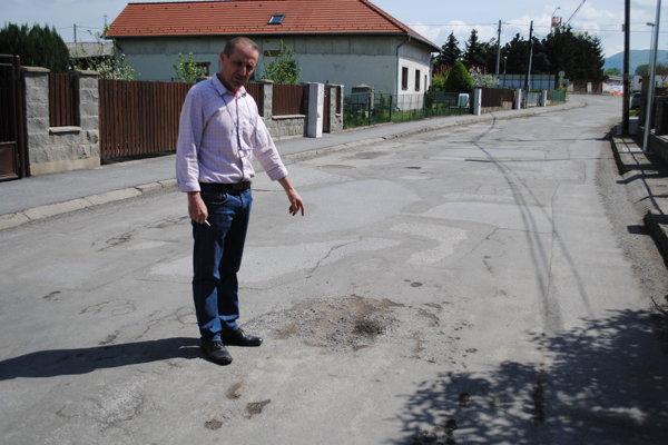 Ján Fecko ukazuje na krátery na ceste.