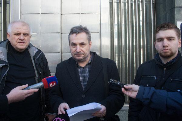 Ondrej Dostál (v strede) na brífingu po podaní trestného oznámenia na premiéra Fica.