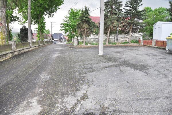 Parkovisko acesta pri cintoríne snovou vozovkou.⋌