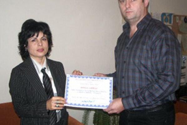 Učebnbice Ivety Staníkovej Martinkovej prevzal z jej rúk riaditeľ ZŠ  v Rajci Mariín Paprskár.