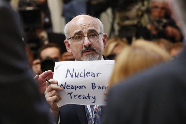 """Muž držal plagát s nápisom """"Dohoda o zákaze jadrových zbraní""""."""