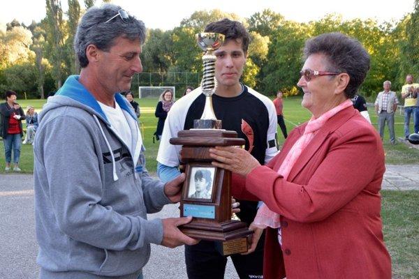 Putovný pohár Memoriálu Ľuboša Greguša odovzdáva Mária Gregušová Milanovi Gregušovi. V strede najlepší brankár turnaja Michal Jamrich.