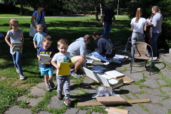 Zatiaľ čo ockovia montujú policu, deti už nosia knihy.