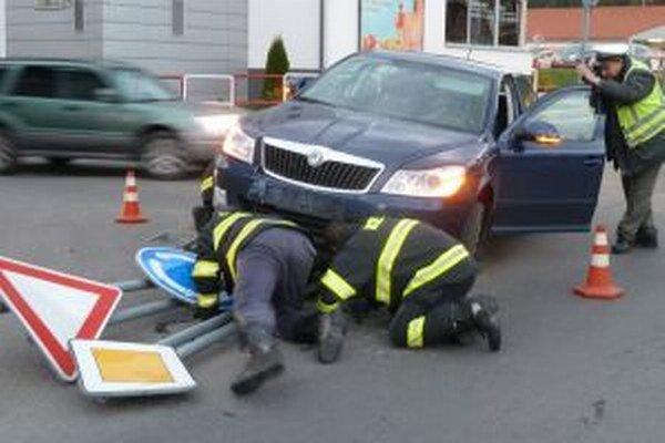 Hasiči sa snažia vybrať dopravné značky, ktoré bránia odjazdu auta.