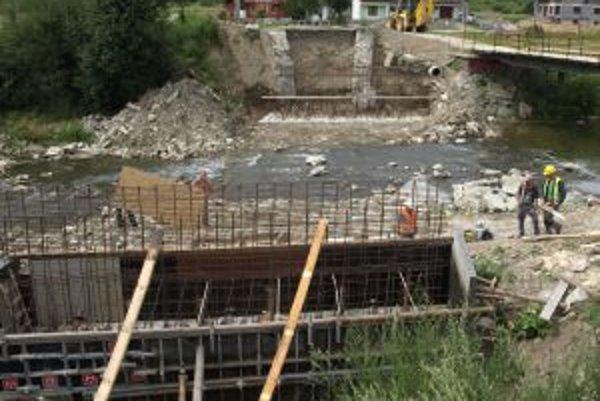 Robotníci stavajú piliere na nový most.