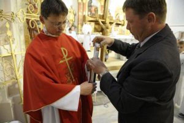 Starosta Ján Kamas spolu s kňazom Štefanom Tukom vkladajú do kovového púzdra odkaz pre budúce generácie.