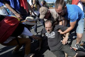 Demonštranti pomáhajú vstať mužovi, ktorý spadol, keď sa pokúšal prejsť cez zástup policajtov.
