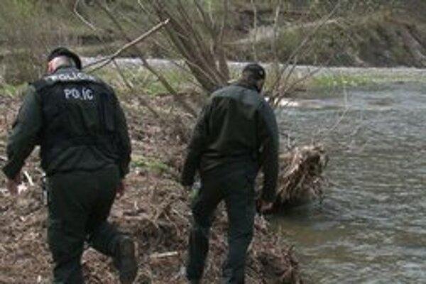 Policajti hľadajú na brehu rieky odpad, ktorý tam nahádzala lekárka.