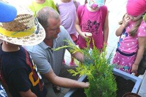 Pri sadení záhradníkovi Jánovi Čambrovi pomáhali aj deti zenvironmentálneho tábora.