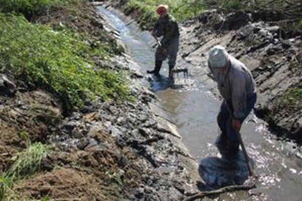 Na čistenie potoka s lopatami v rukách sa v dedine našli len dvaja chlapi. Keby bolo viac dobrovoľníkov, práca by išla rýchlejšie.