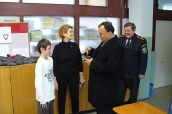 Primátor Peter Baláž za prítomnosti náčelníka mestskej polície Ľudovíta Dušu a riaditeľky školy Márie Bezákovej odovzdáva darček Tomášovi Hanovi.