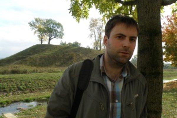 Archeológ Milan Horňák, v pozadí prírodný útvar Atilov hrob, na ktorom sa nachádza známe nálezisko z mladšej doby kamennej.