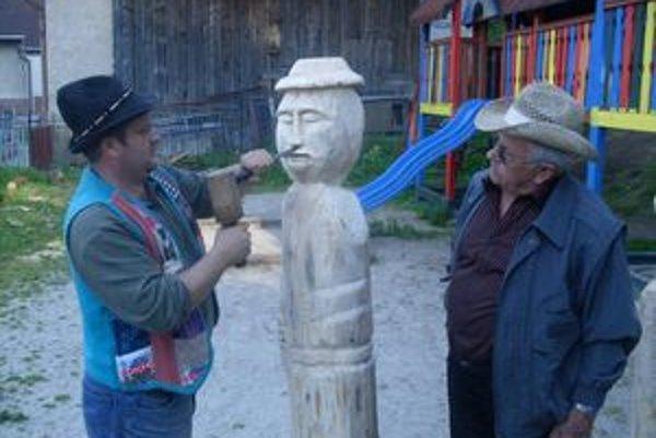 Miestny rezbár Ivan Blahušiak pri  vyrezávaní plastiky vidiečana v životnej veľkosti. Pri práci ho sleduje Ján Petráško, ľudový umelec z Veľkého Čepčína.