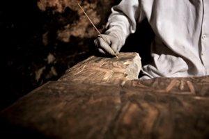 Archeológ si prezerá artefakt vo vnútri faraónskej hrobky.