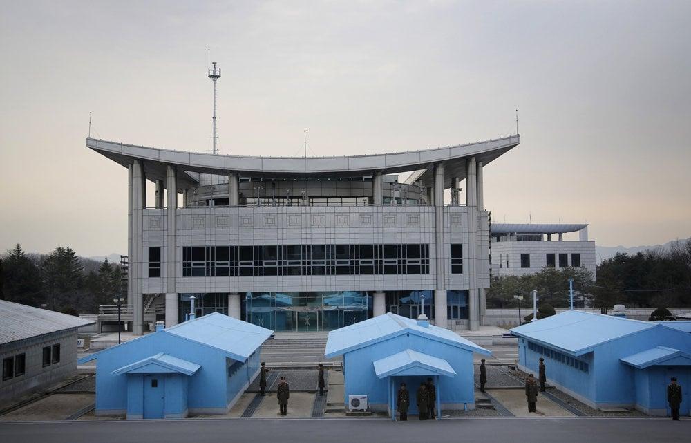 Juhokórejská budova v demilitarizovanej zóne, pred ňou strážiaci severokórejskí vojaci otočení smerom k Severnej Kórei.