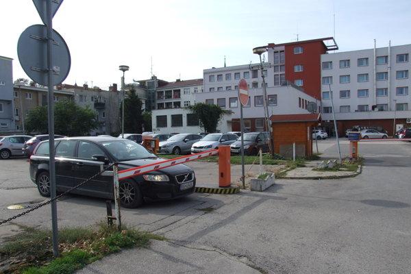 Pred parkoviskom sú rampy. Vzadu je hotel, vľavo bytovka.