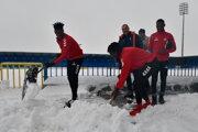 Na snímke vpredu futbalisti FK Senica Edmond Addo (vľavo) a Zezinho (vpravo) odhŕňajú sneh.