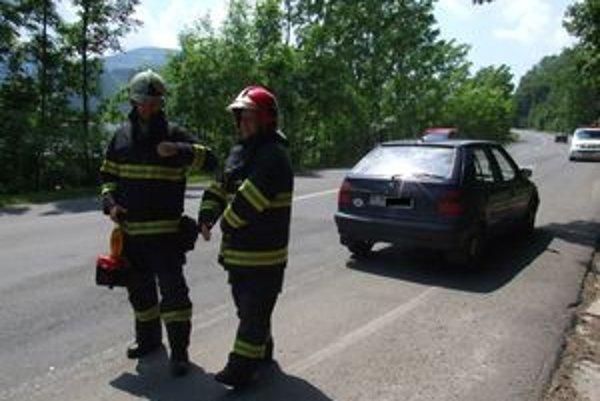 Hasiči zabezpečili miesto nehody, za nimi auto, ktoré sa zrazilo s medveďom.