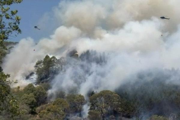 Vrtuľníky hasia požiar v blízkosti rezidenčnej oblasti.