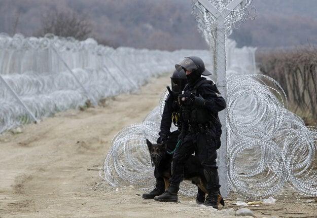 Českí  policajti stoja vedľa dvoch radov ostnatého drôtu na hraniciach Grécka a Macedónska.