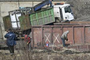 Rozpálené časti vagónov odvážajú za pomoci nákladného auta s mechanickou rukou.