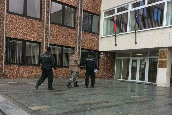 Na snímke muž obvinený z pokusu o vraždu (v strede) prichádza v sprievode policajtov na Okresný súd v Trenčíne.