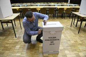 Predseda okrskovej volebnej komisie v Ilave razítkuje urnu pred začiatkom prezidentských volieb 2019.