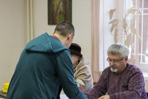 Člen okrskovej volebnej komisie kontroluje totožnosť voliča na otvorenom oddelení v Ústave na výkon väzby a Ústave na výkon trestu odňatia slobody v Bratislave.