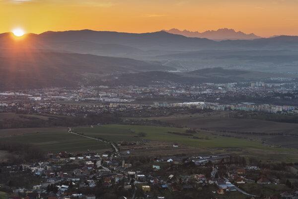 V popredí obec Ruská Nová Ves, uprostred Prešov a vpravo hore Vysoké Tatry v posledných lúčoch slnka.