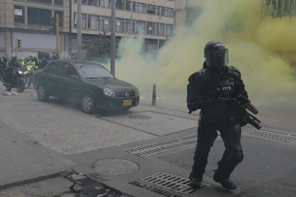 Príslušnk bezpečnostných síl v priebehu zásahu proti demoštrantom v Bogote.