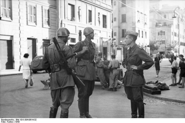 1943: Talianskí vojaci s útočnými puškami na postoch v meste, v pozadí sú nemeckí vojaci.