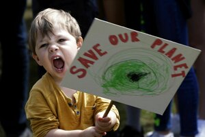 Chlapec drží transparent počas klimatického protestu v Londýne.