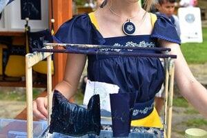 Žiačka Základnej školy v Badíne ukazuje proces výroby modrotlače.