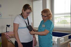Pacientka Andrea Orolinová (vľavo) ukazuje spôsob aplikácie lieku.
