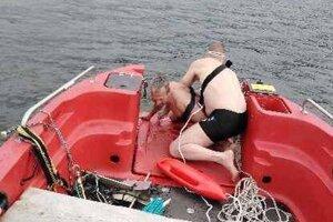 Vysileného Poliaka ťahá do člna ďalší plavec.