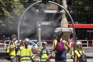 Deti sa  osviežujú vodnou hmlou počas horúceho letného na námestí SNP v Bratislave.