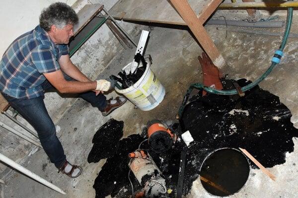 Geochemik Nafta, a.s., Pavol Polesňák odoberá vzorky z priesaku prírodnej ropy v pivnici rodinného domu.