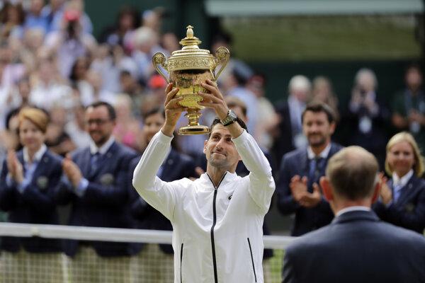 Novak Djokovič dvíha nad hlavu víťaznú trofej vo Wimbledone 2019.