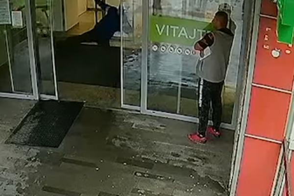 Vandal kopal do dverí, vpravo svedok incidentu.