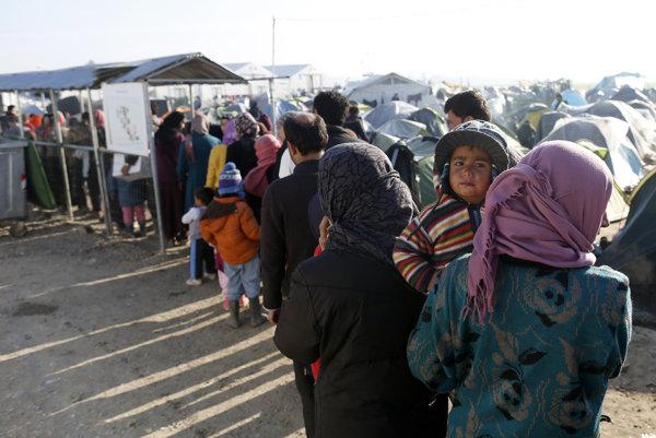 Utečenci v gréckom tábore Idomeni čakajú v radoch na obed.