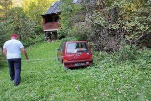 Od auta vedú k stromu šnúry, zrejme si tu niekto pomocou auta ohradil pozemok.