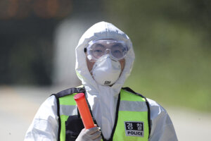 Juhokórejský policajt s ochrannou maskou.