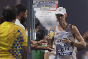 Matej Tóth počas MS v atletike 2019, nápoje mu podáva tréner Matej Spišiak.