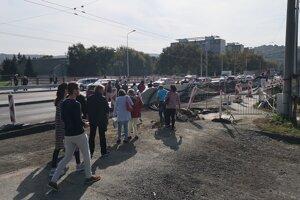 Ľudia obchádzajú zábrany po ceste popri kamiónoch.
