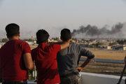 Ľudia sledujú dym stúpajúci po ostreľovaní tureckou armádou.