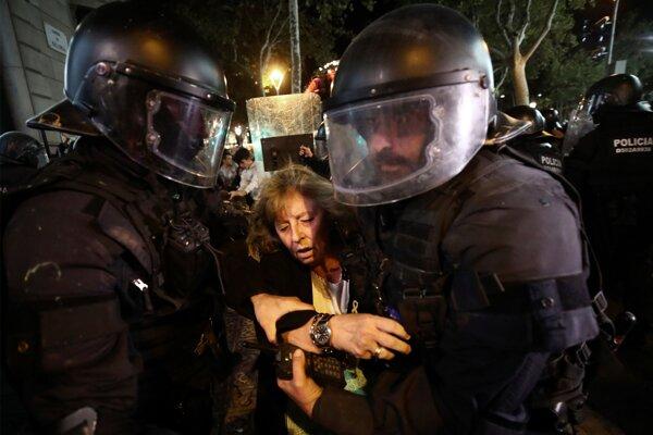 Na snímke príslušníci poriadkových jednotiek štátnej polície odvádzajú staršiu ženu počas neutíchajúcich protestov v uliciach Barcelony proti odsúdeniu deviatich bývalých katalánskych lídrov v Barcelone 15. októbra 2019.