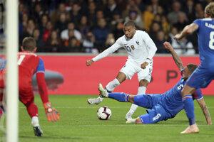 Kylian Mbappé(uprostred) kope do lopty cez Ragnara Sigurdssona z Islandu v prípravnom futbalovom zápase Francúzsko - Island v Guingampe 11. októbra 2018.