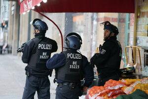 Policajti v strehu na uliciach Friedrichstraße a Kochstraße v centre Berlína.