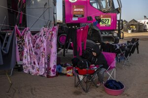 Žena perie a vešia prádlo vedľa kamióna počas voľného dňa na Rely Dakar.